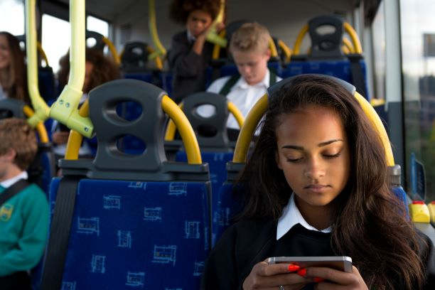 PIC - Teenager playing on phone on bus