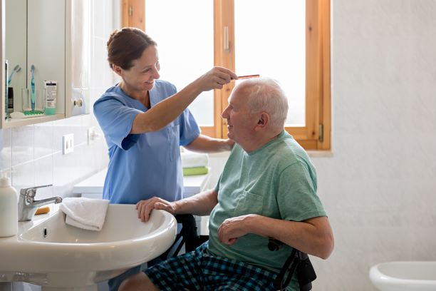 Older man in bathroom with care worker who is brushing his hair